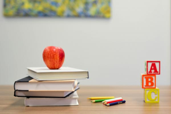 Image of an apple on books on a table with colouring pencils and letter blocks