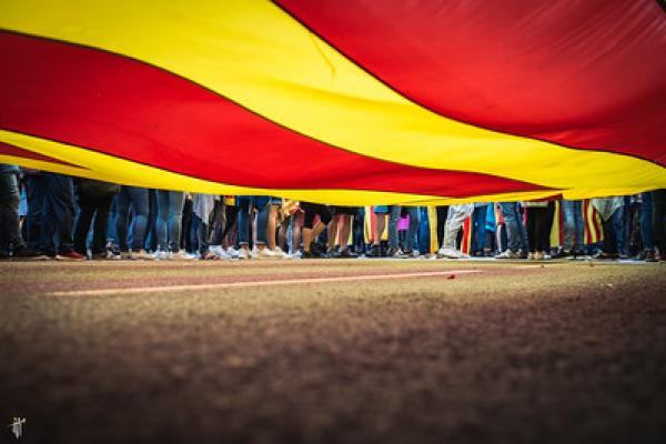 Image of people's legs and feet under red and yellow flag